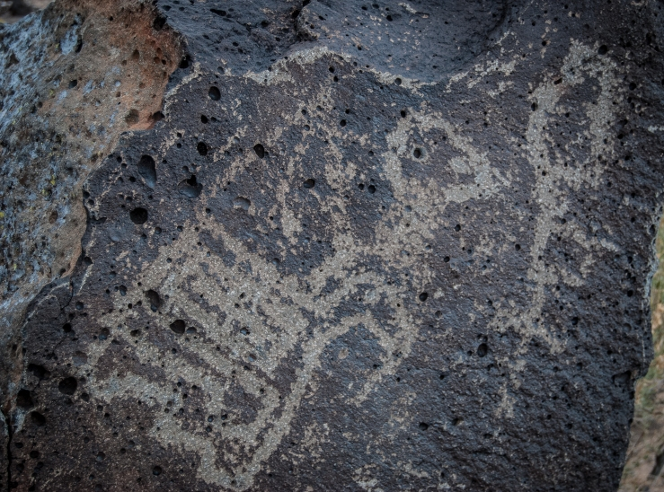 Let's play Petroglyph Pictionary: I see a wild turkey chasing a man in a top hat. Thoughts?